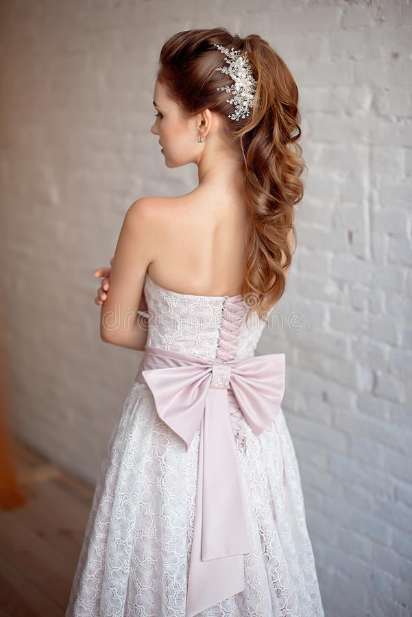 Porträt des schönen luxuriösen weiblichen Modells mit dem Mittelbraunhaar in einem langen fashinable Kleid, das im Raum steht stockbilder
