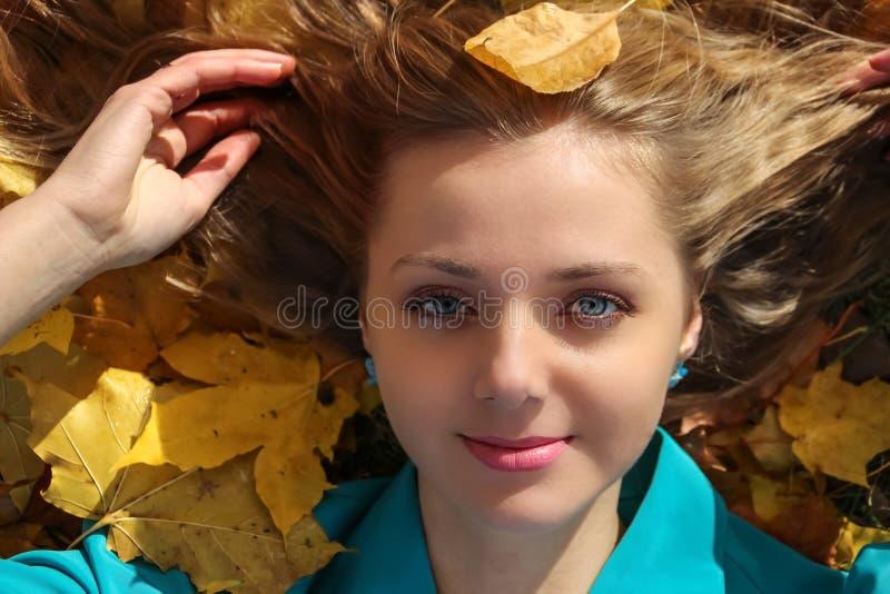 Porträt des schönen Mädchens, das, liegend auf Gras mit gelben Ahornblättern im Herbst lizenzfreies stockbild
