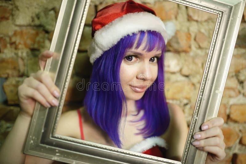 Porträt des schönen Mädchens in der Klage Santa Claus, die Stangenbrot hält stockfotografie