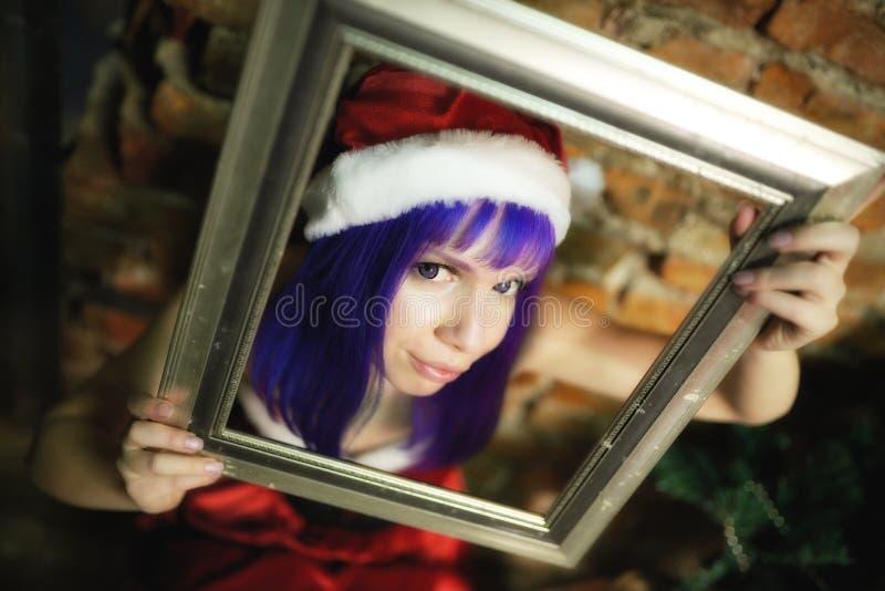 Porträt des schönen Mädchens in der Klage Santa Claus, die Stangenbrot hält stockfotos