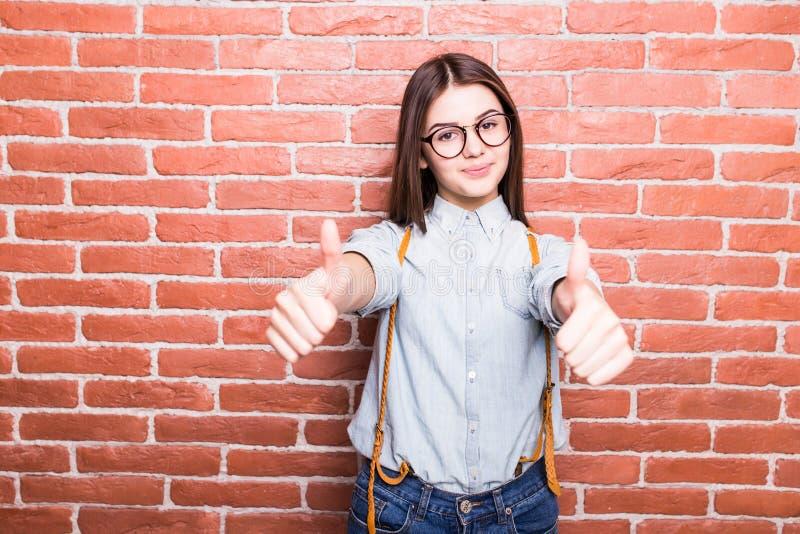 Porträt des schönen Mädchens in der zufälligen Kleidung, die OKAYzeichen zeigt, stockfotografie