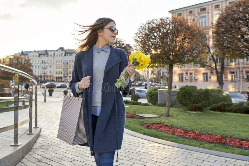Porträt des schönen Mädchens gehend in Stadt, in junge Frau mit Blumenstrauß von gelben Blumen und in Einkaufstasche, Hinterg stockfotos