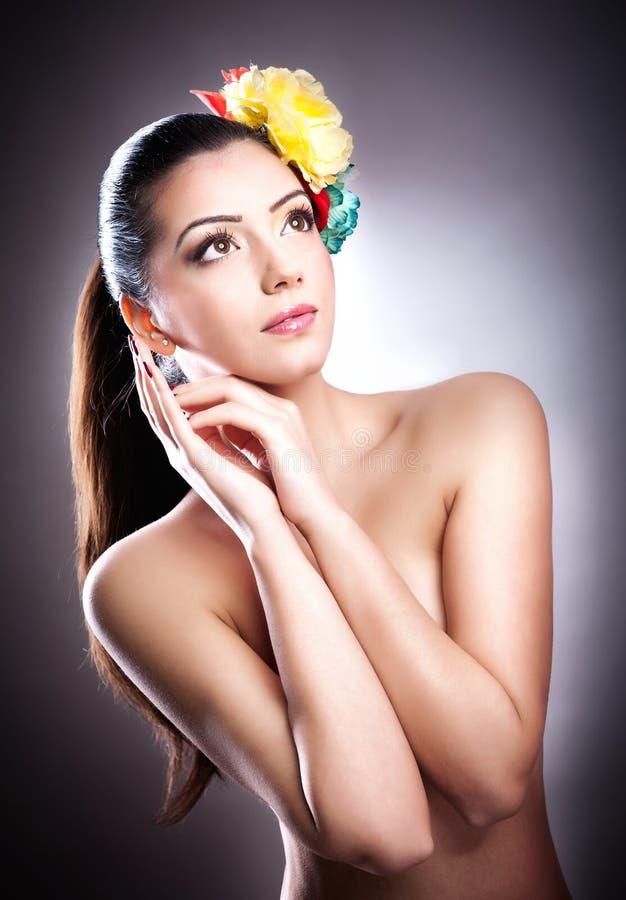 Porträt des schönen Mädchens im Studio mit Blumen in ihrem Haar lizenzfreie stockbilder