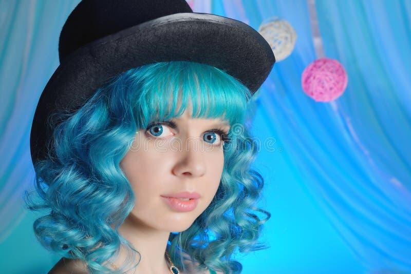 Porträt des schönen Mädchens mit dem blauem gelockten Haar und Hut lizenzfreie stockfotografie