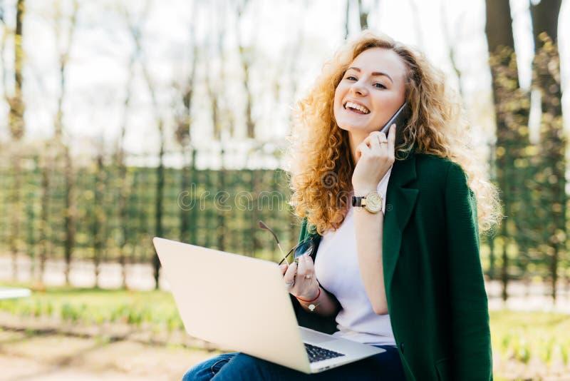 Porträt des schönen Mädchens, welches das flaumige blonde Haar hält Smartphone in einer Hand und in der Sonnenbrille in anderem H lizenzfreie stockfotos
