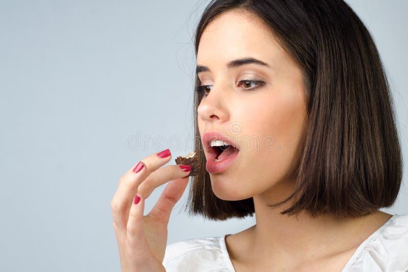 Porträt des schönen Mädchens, welches die Schokoladenplätzchen lokalisiert isst lizenzfreie stockfotografie