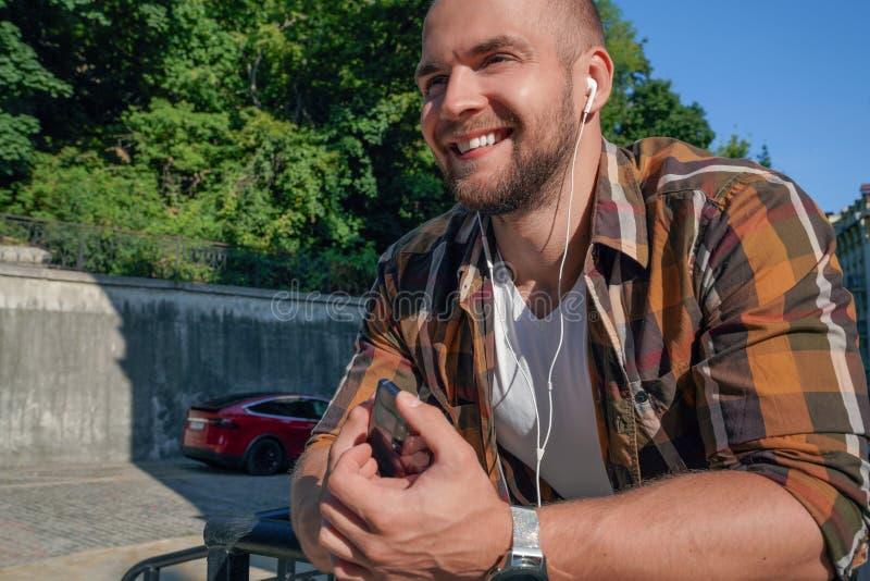 Porträt des schönen mutigen bärtigen Kerlfreien-Holdingmobiltelefons in seiner Hand mit Kopfhörern in seinen Ohren und in hörende lizenzfreie stockfotografie