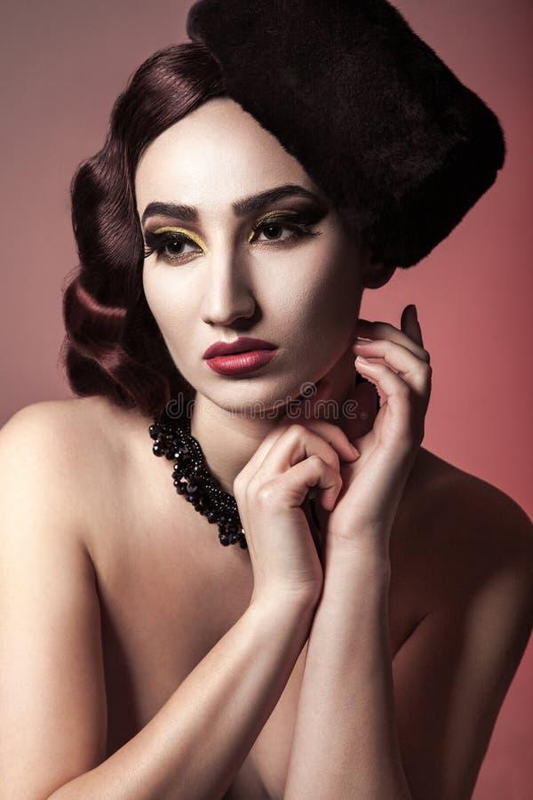 Porträt des schönen nackten Mode-Modells mit gewellter Frisur, Hut und dunklem Make-up auf rotem Hintergrund lizenzfreies stockbild