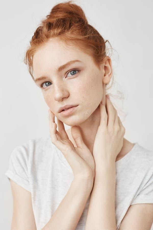 Porträt des schönen natürlichen Rothaarigemädchens über dem weißen Hintergrund, der staright Kamera betrachtet stockfotografie