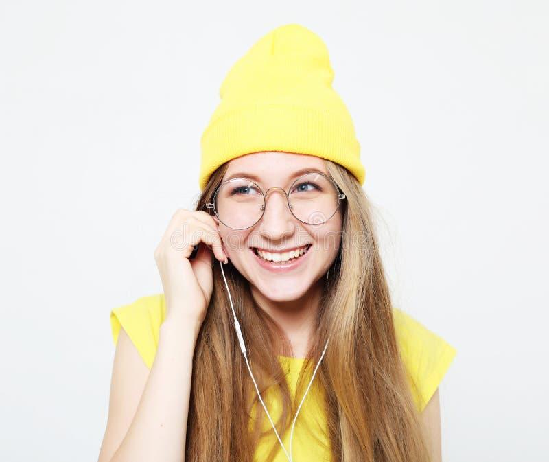 Porträt des schönen netten Mädchens mit Kopfhörern mit dem lächelnden Lachen des langen Haares, Kamera betrachtend stockbild