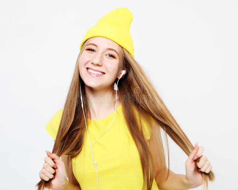 Porträt des schönen netten Mädchens mit Kopfhörern mit dem lächelnden Lachen des langen Haares, Kamera betrachtend lizenzfreies stockfoto