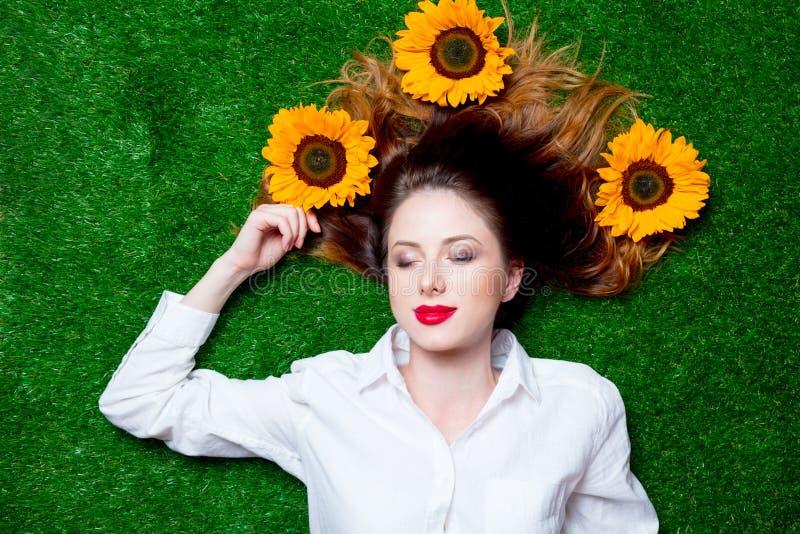 Porträt des schönen rothaarigen Mädchens mit Sonnenblumen lizenzfreie stockfotos