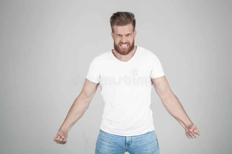 Porträt des schönen sexy bärtigen Mannes, der seine Energie zeigt und in camera schreit er steht vor dem Wei? lizenzfreie stockfotografie