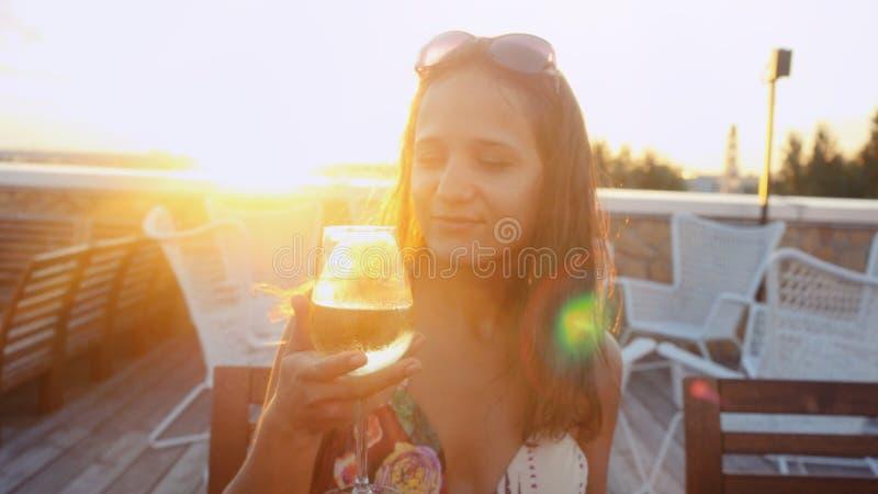 Porträt des schönen trinkenden Cafés des Weins der jungen Frau draußen am Sonnenschein während des Sonnenuntergangs in der Sommer lizenzfreie stockfotografie