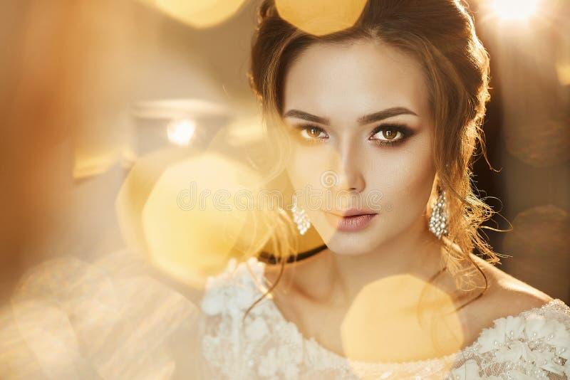 Porträt des schönen und modernen braunhaarigen vorbildlichen Mädchens, in einem Spitzekleid stockbild