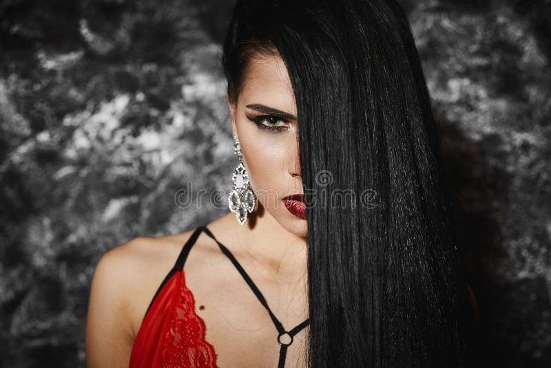 Porträt des schönen und modernen Brunettemodellmädchens mit hellem Make-up und mit großen Ohrringen in der roten Wäsche, mit gesc stockbilder