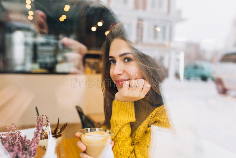 Porträt des schüchternen nachdenklichen Mädchens in gestrickter Strickjacke Kaffee genießend und Straße betrachtend Innenfoto von lizenzfreie stockfotografie