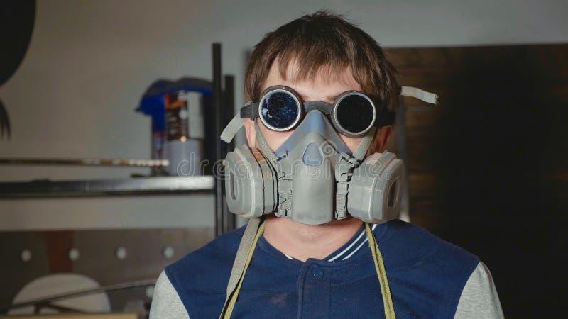 Porträt des Schmiedes in den Schutzgläsern und des Respirators, der Kamera betrachtet stockbilder
