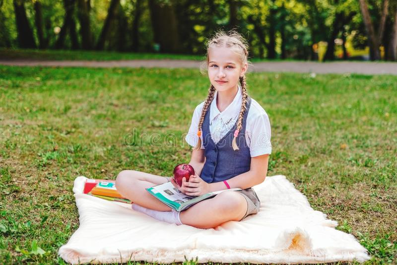 Porträt des Schulmädchenjugendlichen mit den Zöpfen, die im Park auf Bettdecke mit Apfel sitzen stockfotografie