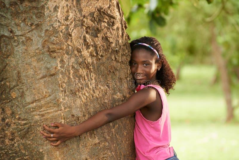 Porträt des schwarzen Ökologemädchens, das Baum und das Lächeln umarmt lizenzfreie stockfotos