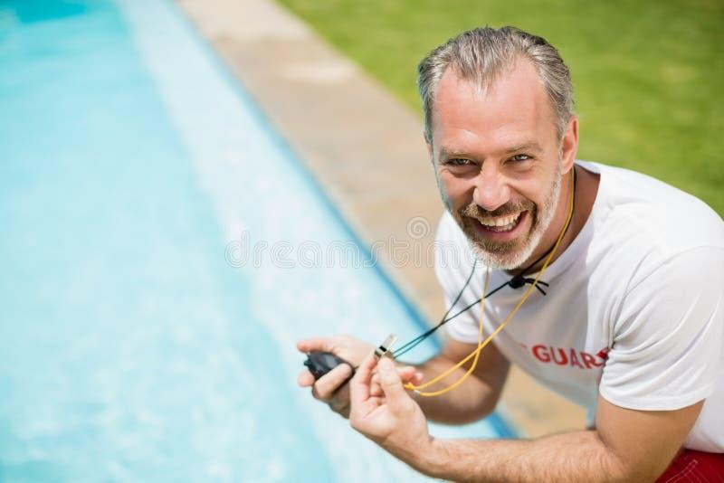 Porträt des Schwimmentrainers Stoppuhr nahe Poolside halten stockbilder