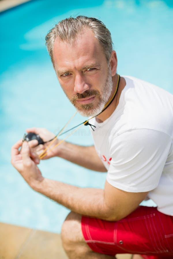 Porträt des Schwimmentrainers Stoppuhr nahe Poolside halten lizenzfreie stockfotos