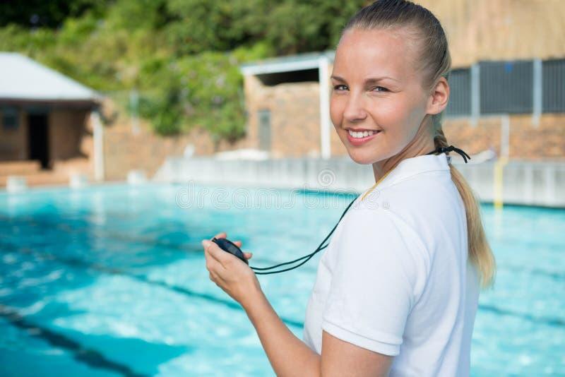 Porträt des Schwimmentrainers Stoppuhr am Poolside halten stockbilder