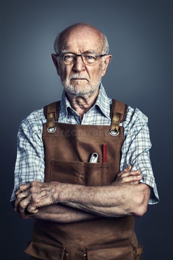 Porträt des Seniors bei der Arbeit stockbild
