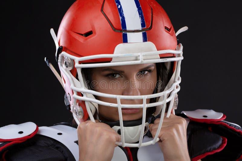 Porträt des sexy attraktiven jungen Mädchens mit einem hellen Make-up in einer Sportausstattung für amerikanischen Fußball stockfotos
