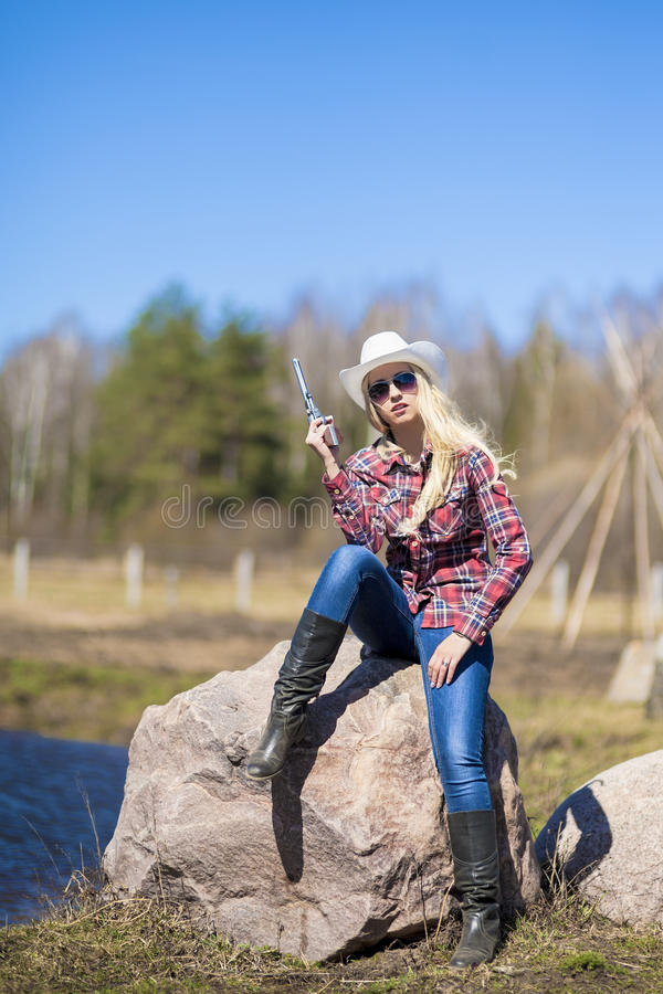 Porträt des sexy blonden Cowgirls mit Gewehr draußen lizenzfreie stockfotografie