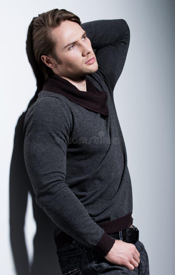 Porträt des sexy jungen Mannes mit der Hand nahe Gesicht stockfotografie