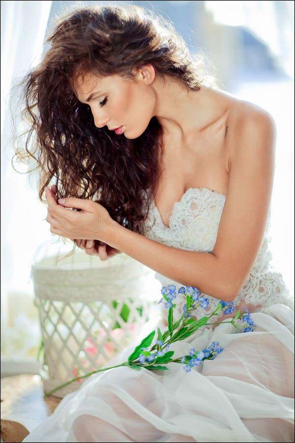 Porträt des sinnlichen gelockten behaarten Mädchens in einem weißen Kleid mit clos lizenzfreie stockfotografie