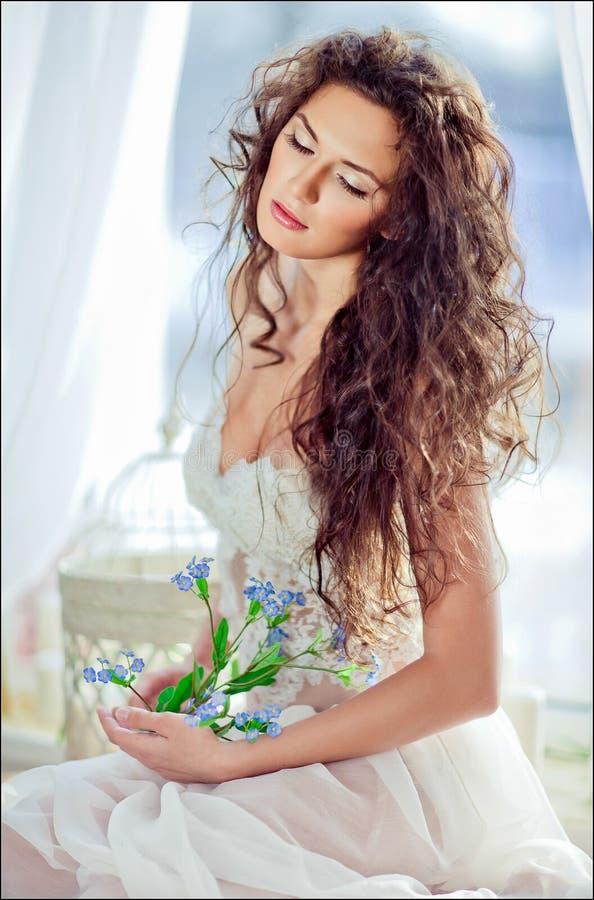 Porträt des sinnlichen gelockten behaarten Mädchens in einem weißen Kleid mit ihr stockbilder