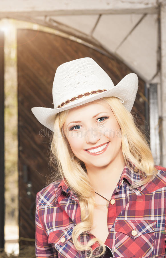 Porträt des sinnlichen lächelnden glücklichen blonden Cowgirls, das Stetson trägt lizenzfreie stockfotos