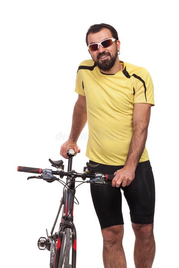 Porträt des smilling Radfahrers mit Sonnenbrille und gelbem Hemd, werfend mit einem Fahrrad auf, lokalisiert auf Weiß lizenzfreie stockfotografie