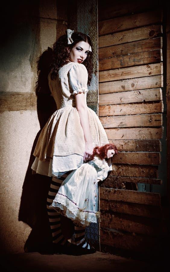 Porträt des sonderbaren furchtsamen Mädchens mit Puppe in der Hand lizenzfreie stockfotografie