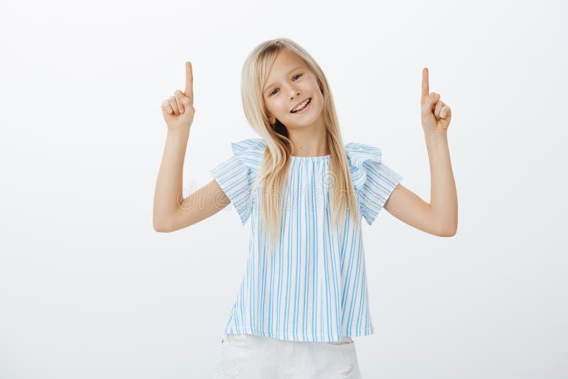 Porträt des sorglosen überzeugten kleinen Kindes mit dem blonden Haar in der stilvollen Ausstattung, Zeigefinger und das Zeigen v stockfotografie