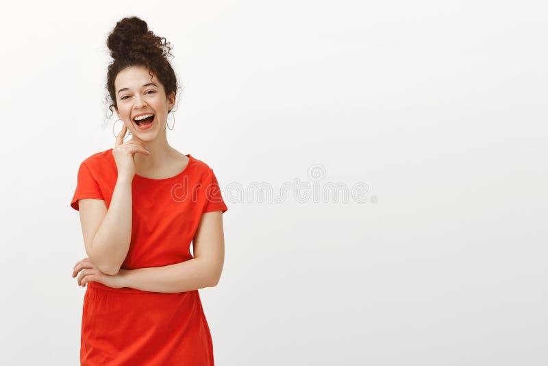 Porträt des sorglosen glücklichen europäischen Mädchens im modischen roten Kleid mit dem gelockten Haar gekämmt im Brötchen, laut lizenzfreie stockbilder