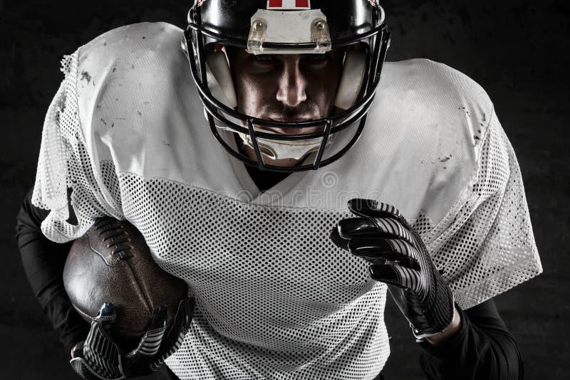 Porträt des Spielers des amerikanischen Fußballs, der einen Ball hält lizenzfreies stockfoto