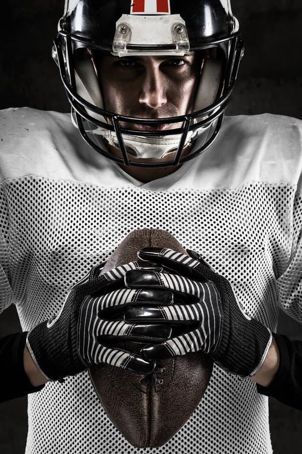 Porträt des Spielers des amerikanischen Fußballs, der einen Ball hält lizenzfreie stockfotografie