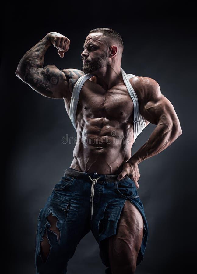 Porträt des starken athletischen Eignungsmannes, der große Muskeln zeigt stockfoto