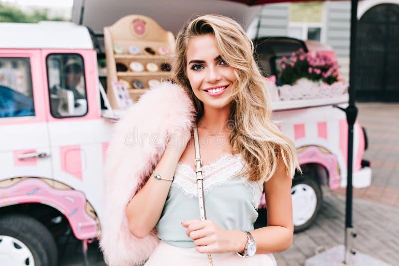 Porträt des Stiftes herauf angeredetes Mädchen mit dem langen blonden Haar auf Retro- Kaffeeautohintergrund Sie hält rosa Pelzsto stockfotografie