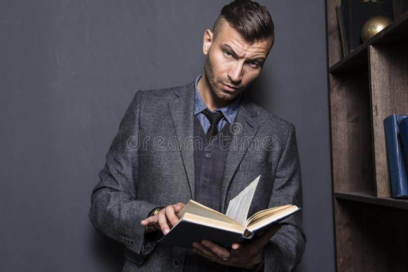 Porträt des stilvollen, eleganten jungen Mannes in der Klage mit Buch Junger gutaussehender Mann liest Buch stockfoto