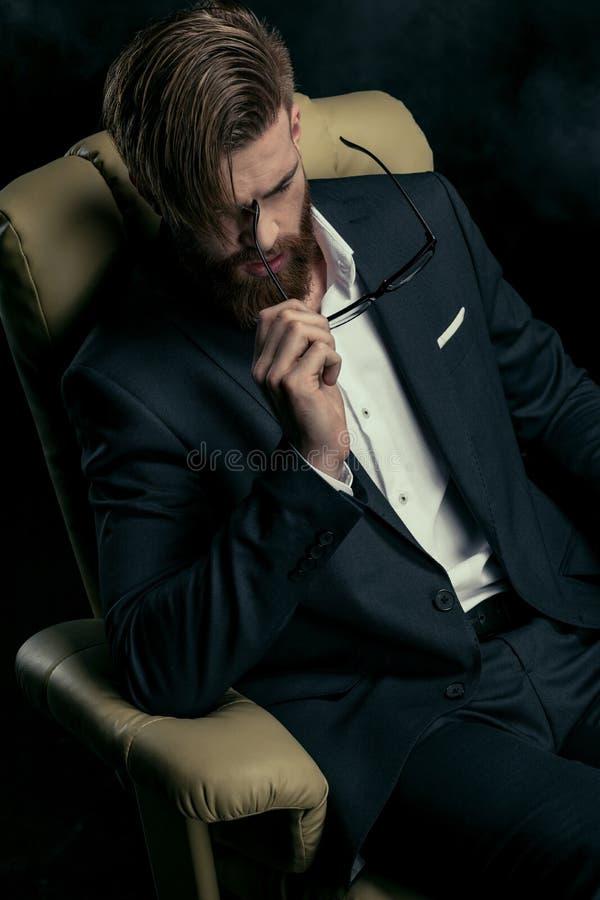 Porträt des stilvollen Geschäftsmannes mit Brillen im Lehnsessel lizenzfreies stockbild