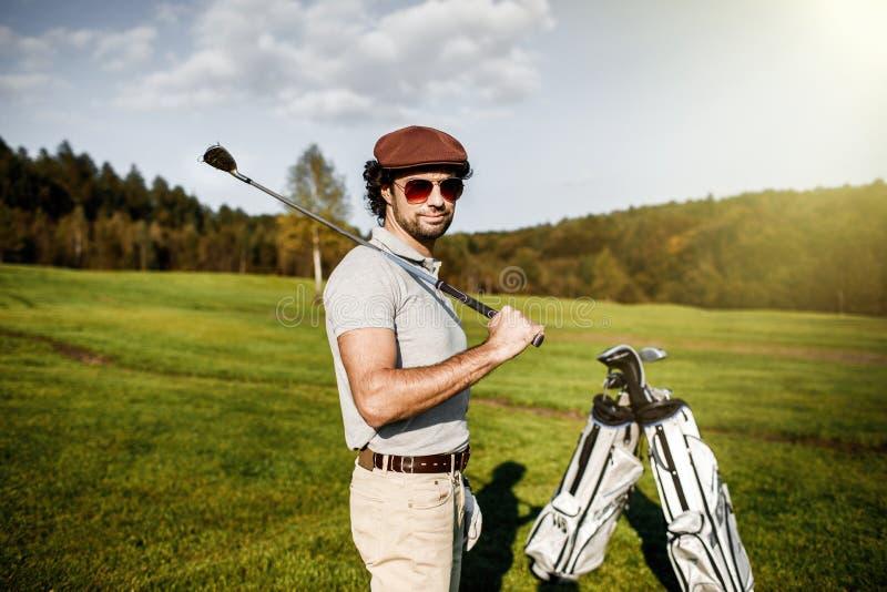 Porträt des stilvollen Golfspielers in den Gläsern, die auf Golfplatz wi stehen stockfoto