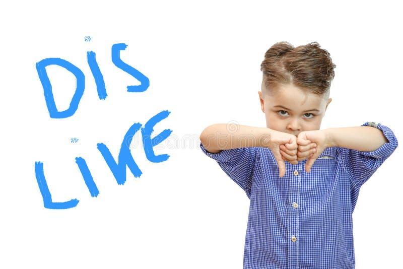 Porträt des stilvollen hübschen Jungen lokalisiert auf weißem Hintergrund Junge, der unten Daumen zeigt stockfotografie