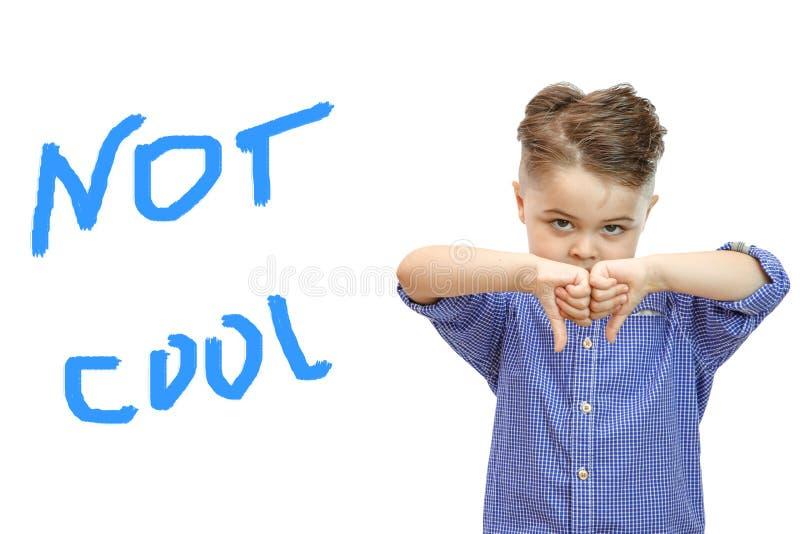 Porträt des stilvollen hübschen Jungen lokalisiert auf weißem Hintergrund Junge, der unten Daumen zeigt lizenzfreie stockfotografie