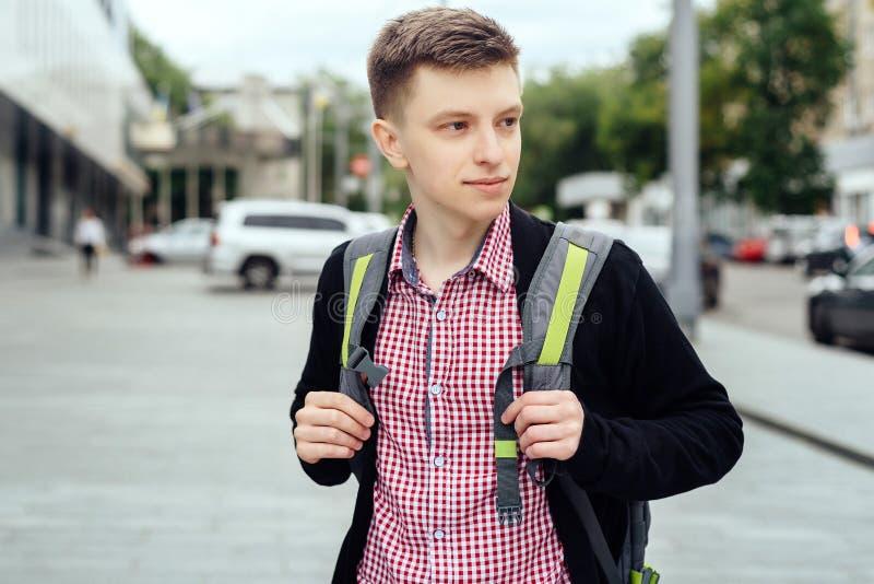 Porträt des stilvollen jungen Mannes im karierten Hemd und in der Jacke mit Rucksack draußen gehend in die Stadt Mitteilung oben  lizenzfreies stockfoto