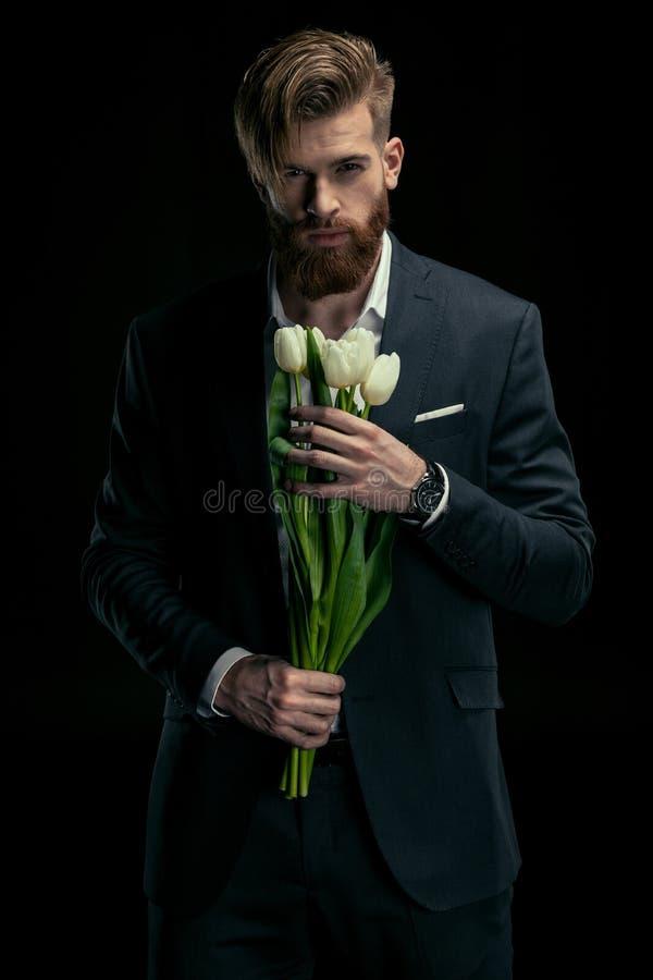 Porträt des stilvollen Mannes in der Klage, die Tulpen für den Tag der internationalen Frauen hält stockfotografie