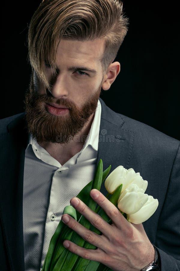 Porträt des stilvollen Mannes im Anzug, der Tulpen am schwarzen Muttertag hält lizenzfreies stockfoto